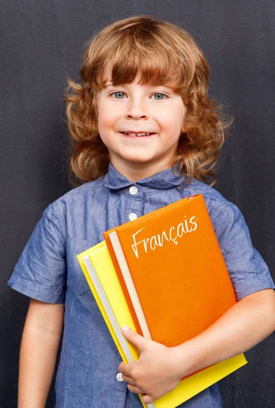petite garçon tenant un livre pour aide aux devoirs en français