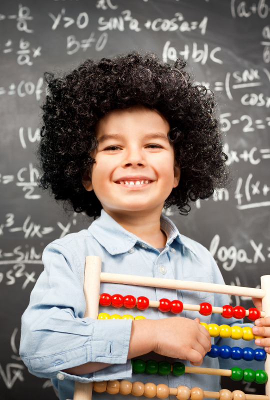 petit garçon tenant un livre pour aide aux devoirs mathématiques